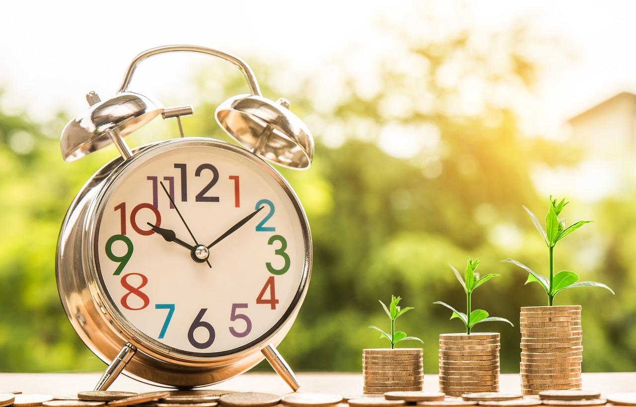 su un tavolo un orologio e tre colonne di monete con sopra i germogli di piante che crescono per indicare la crescita di profitto